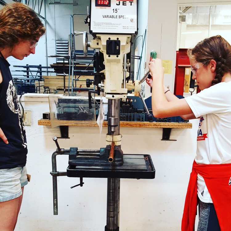 A girl and her instructor use a drill press